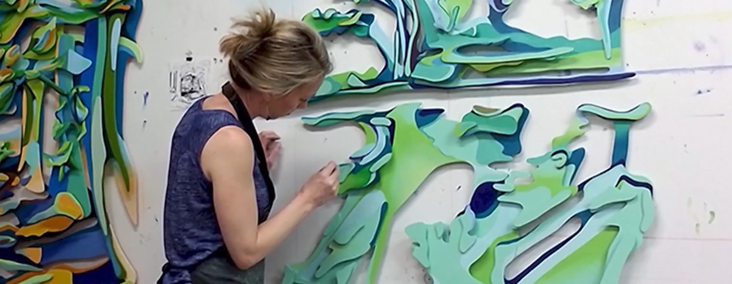 Artist Jenny Hutchinson painting a piece of art mounted on a wall.