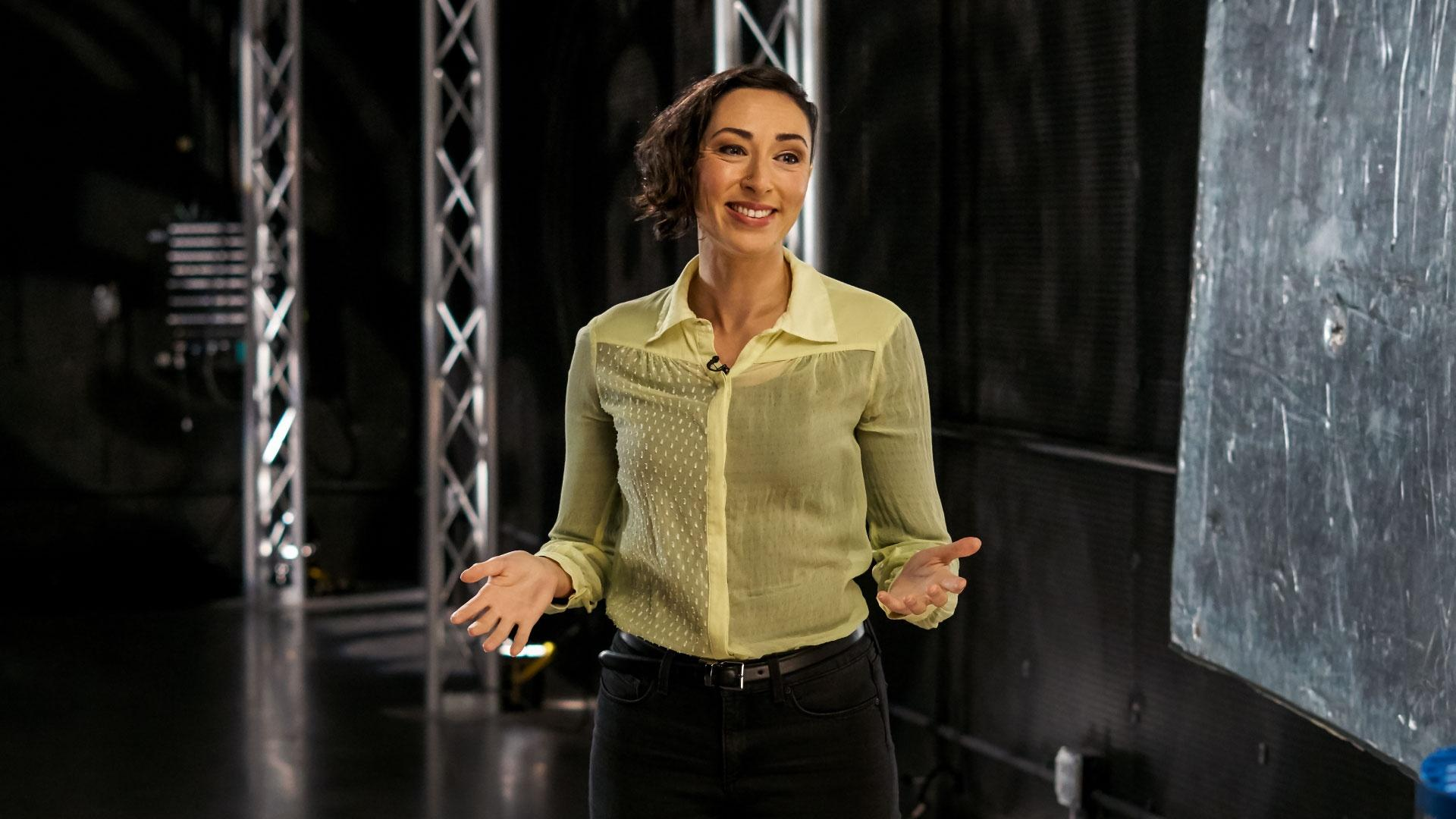 AHA! host Lara Ayad holds her arms out, hands open, while reading from a teleprompter during a shoot.
