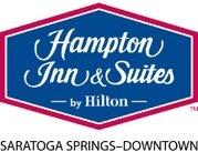 Hampton Inn & Suites by Hilton Logo in white script font in a blue diamond with red outline and the words SARATOGA SPRINGS-DOWNTOWN in black below
