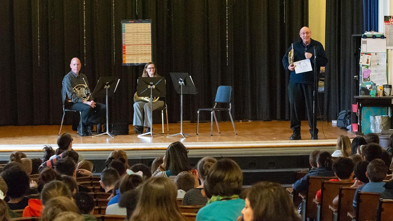 A french horn player from the Buffalo Philharmonic Orchestra talks to students about music