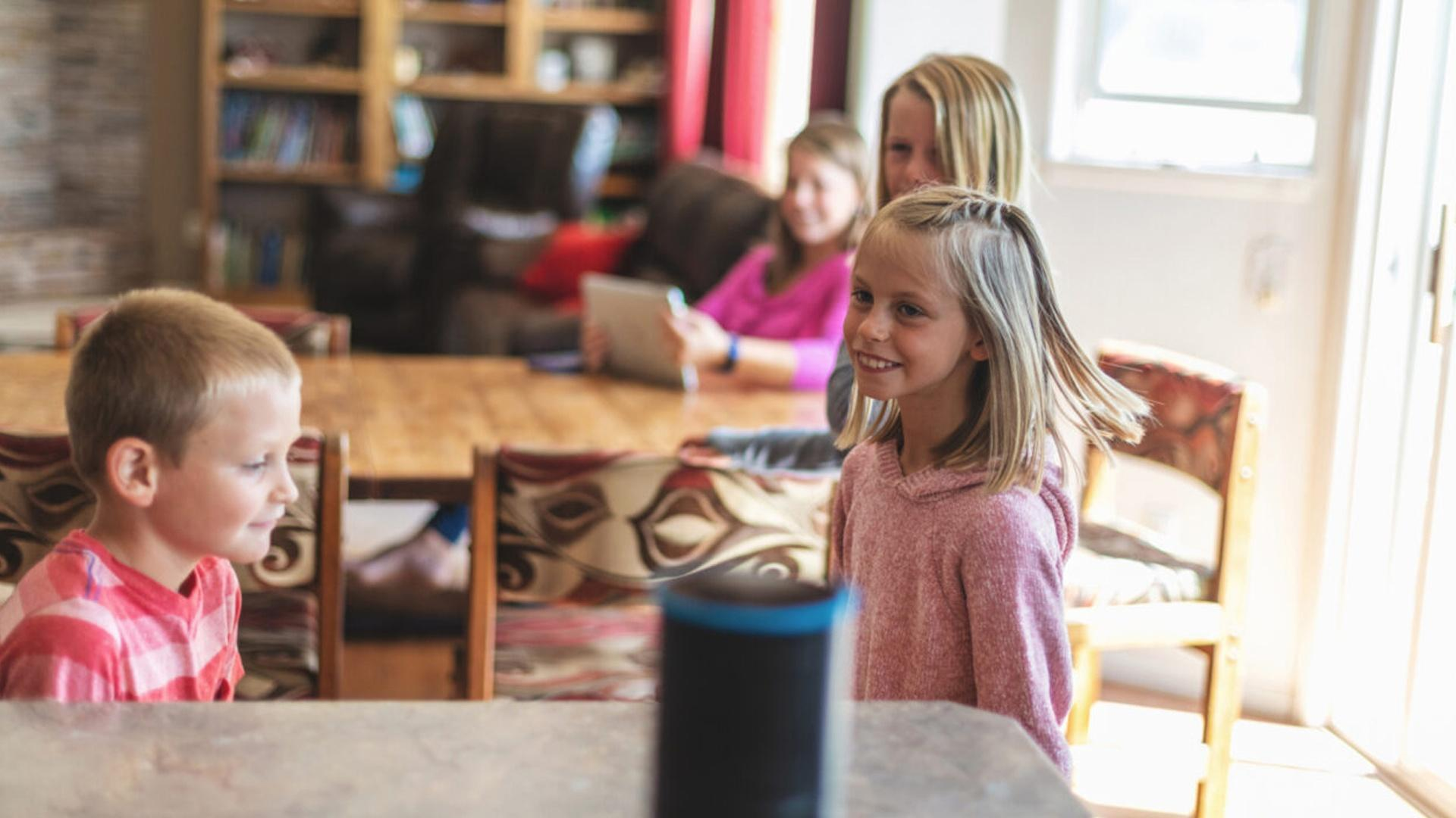 family with young children listening to a smart speaker