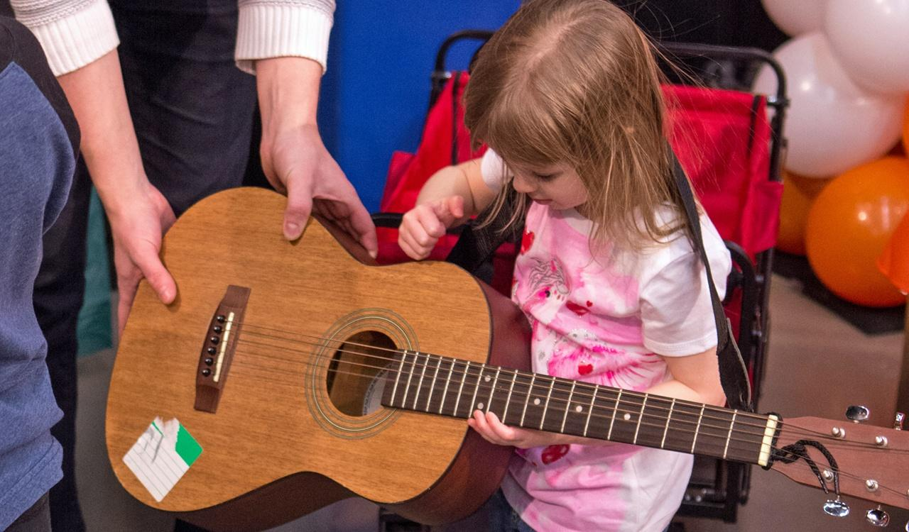 Young girl tries our the guitar with the help of the Community Music School