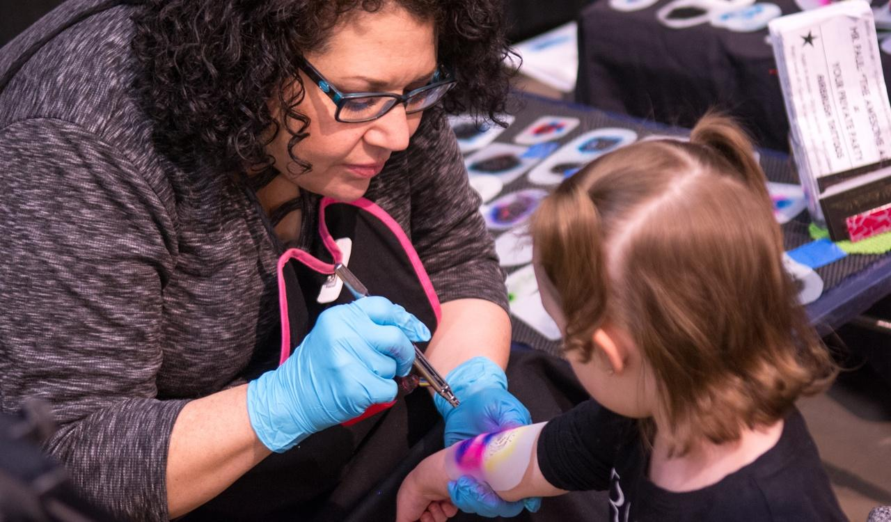 Young girl getting an airbrush tattoo during WNED's Kid Fest
