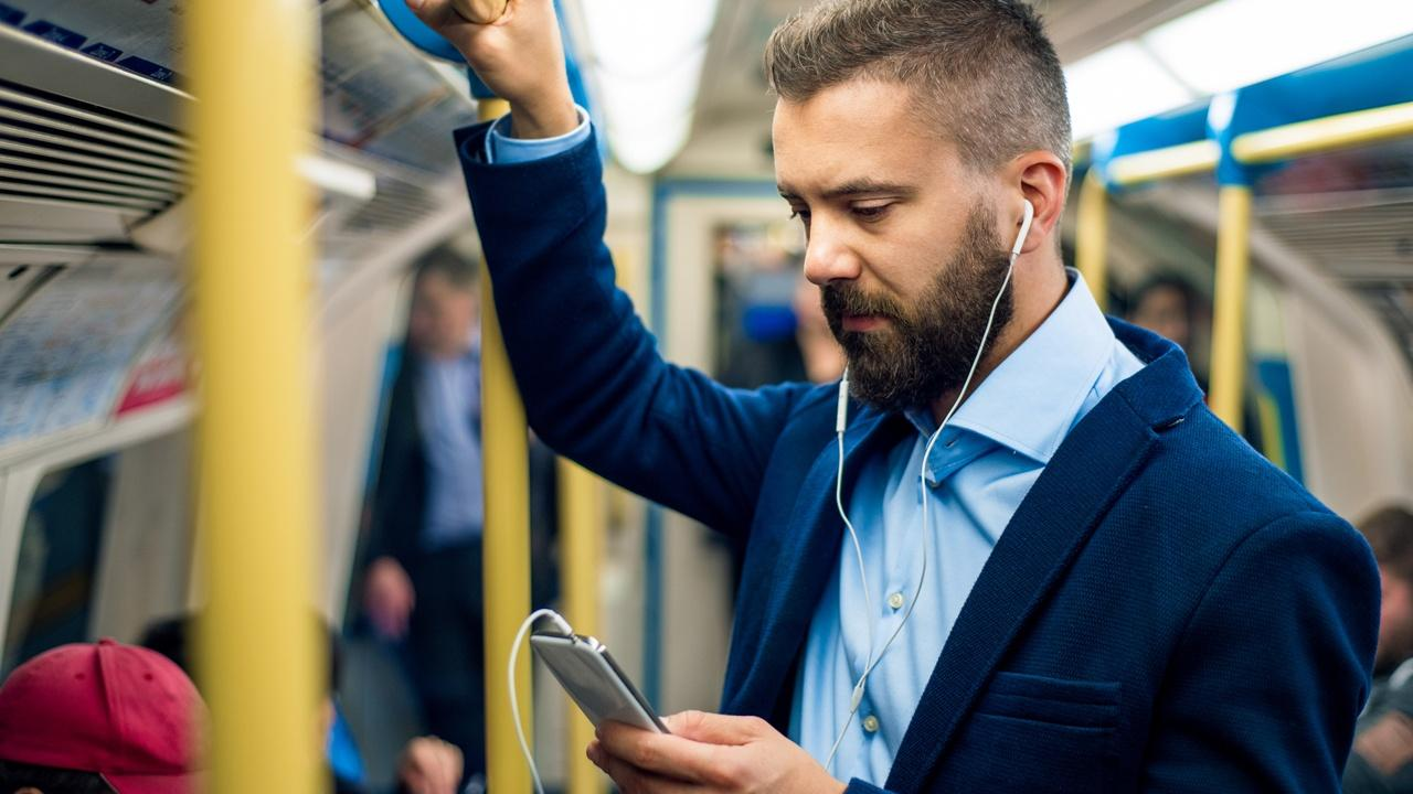 man with earbuds looking at phone while commuting to work