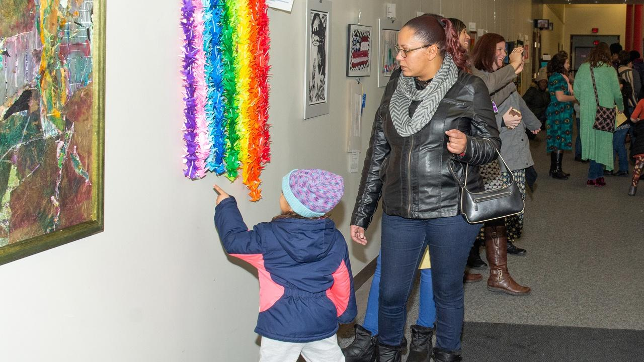 Girl and her Mom admire art during the opening reception