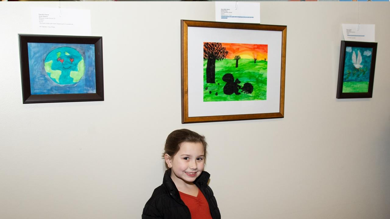 Isabella Rose from Ohio Elementary School poses in front of her watercolor and ink work
