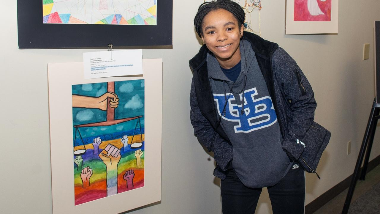 "Artist Lauryn Whiteside poses next to her creation ""Scales of Justice"""