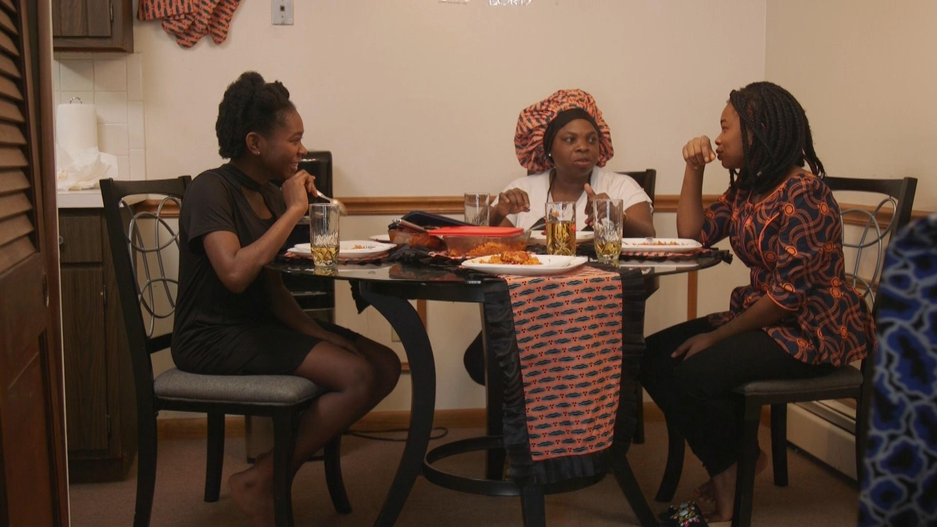 Family at diner table eating Nigerian Jollof RIce