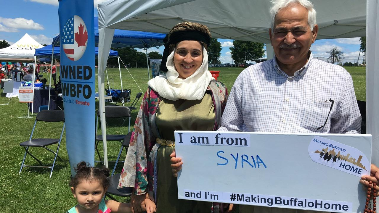 Family from Syria holding a Making Buffalo Home sign