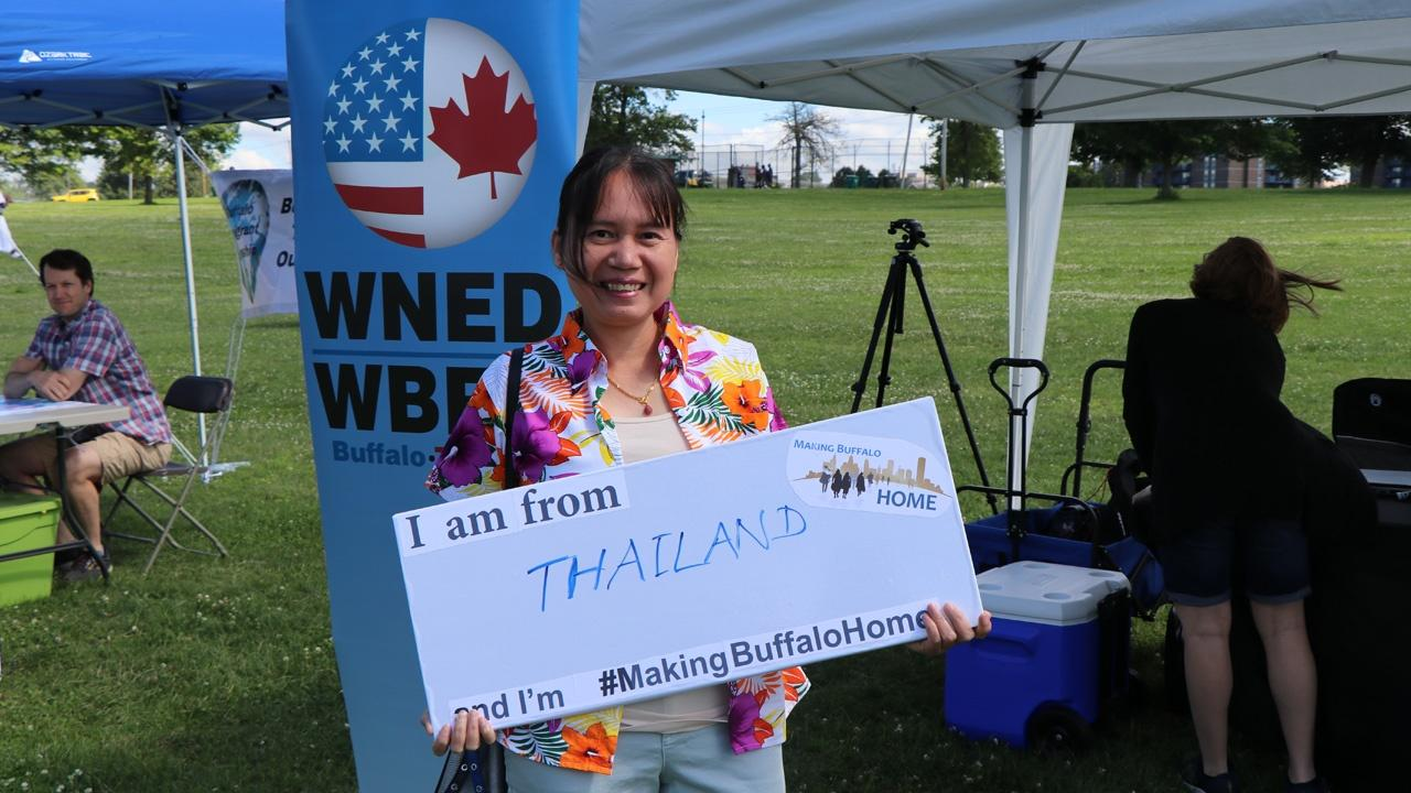 woman from Thailand holding a Making Buffalo Home sign