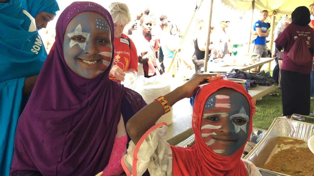 young girls with face paint smiling at Buffalo's World Refugee Day celebrations