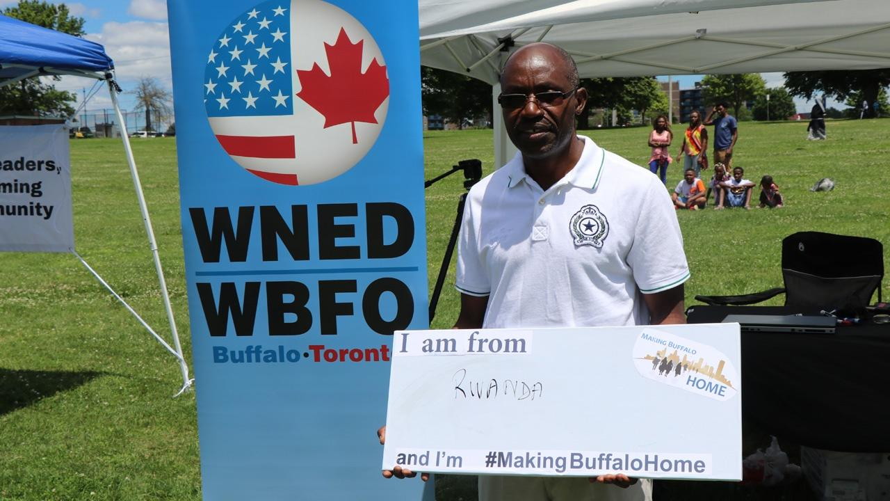 man from Rwanda holding a Making Buffalo Home sign