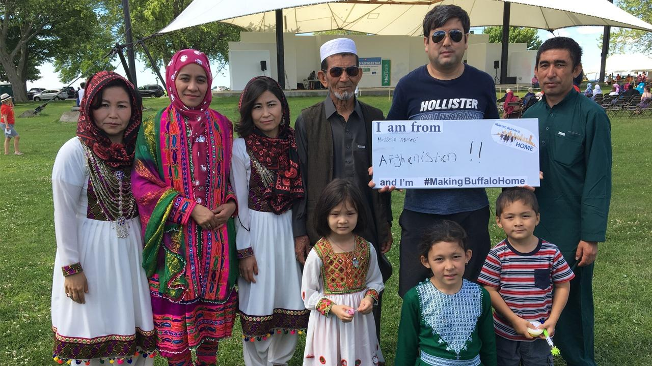 Family from Afghanistan holding a Making Buffalo Home sign