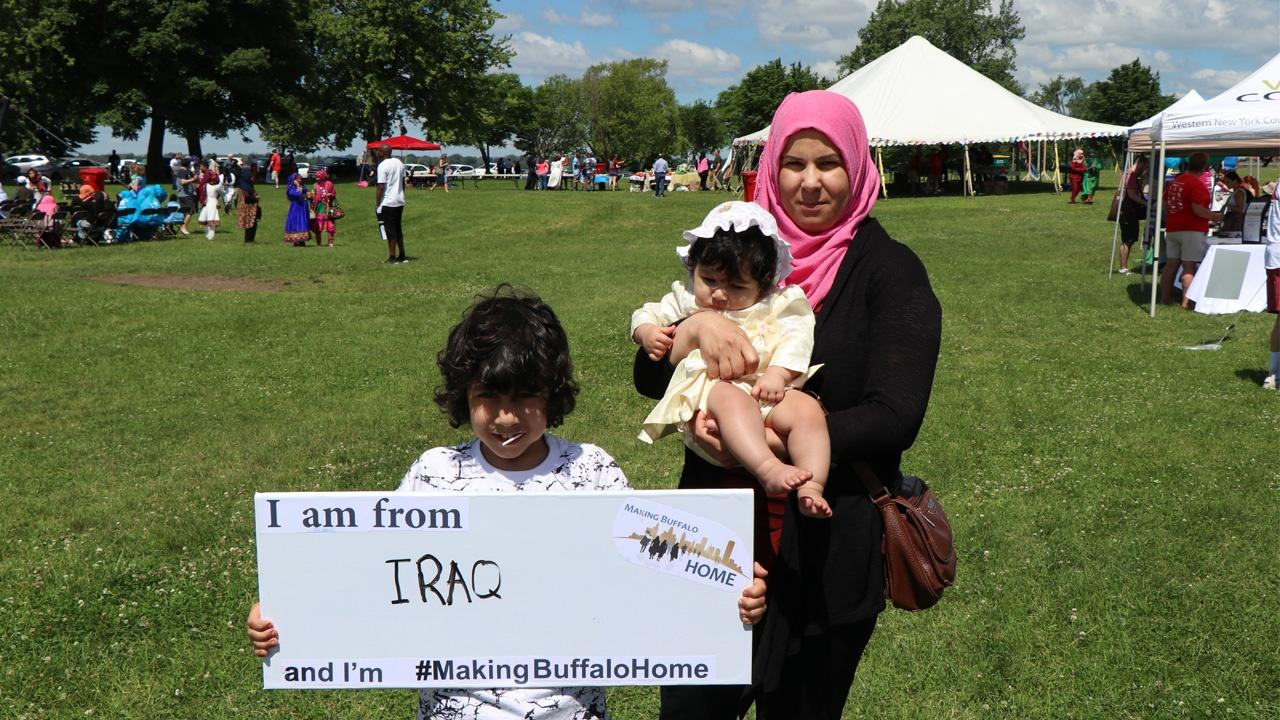 family from Iraq holding a Making Buffalo Home sign