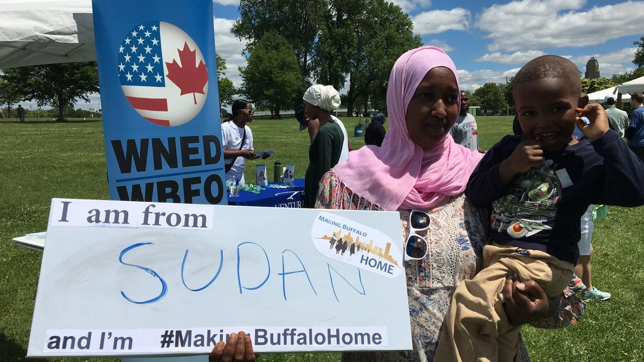 Family from Sudan holding a Making Buffalo Home sign