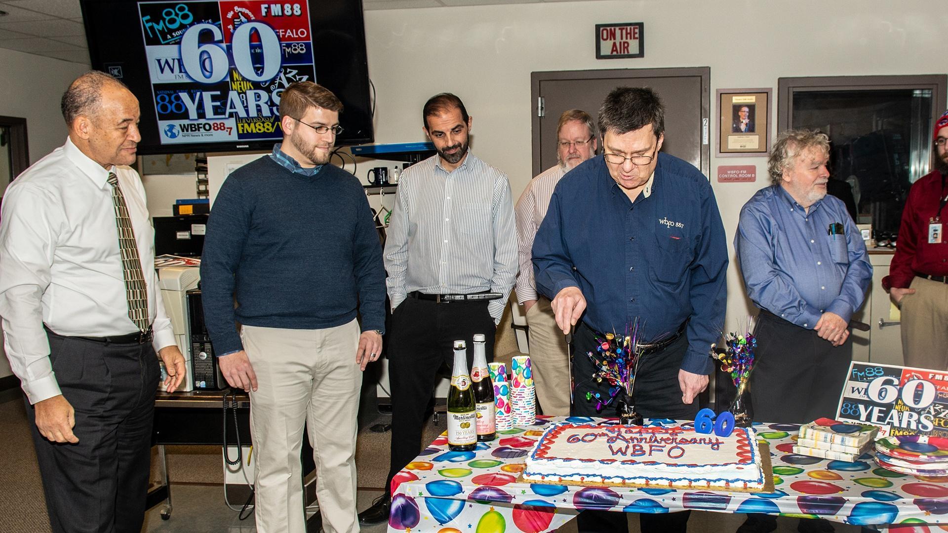 Mark Wozniak the longest current WBFO employee cut the cake to begin the celebration