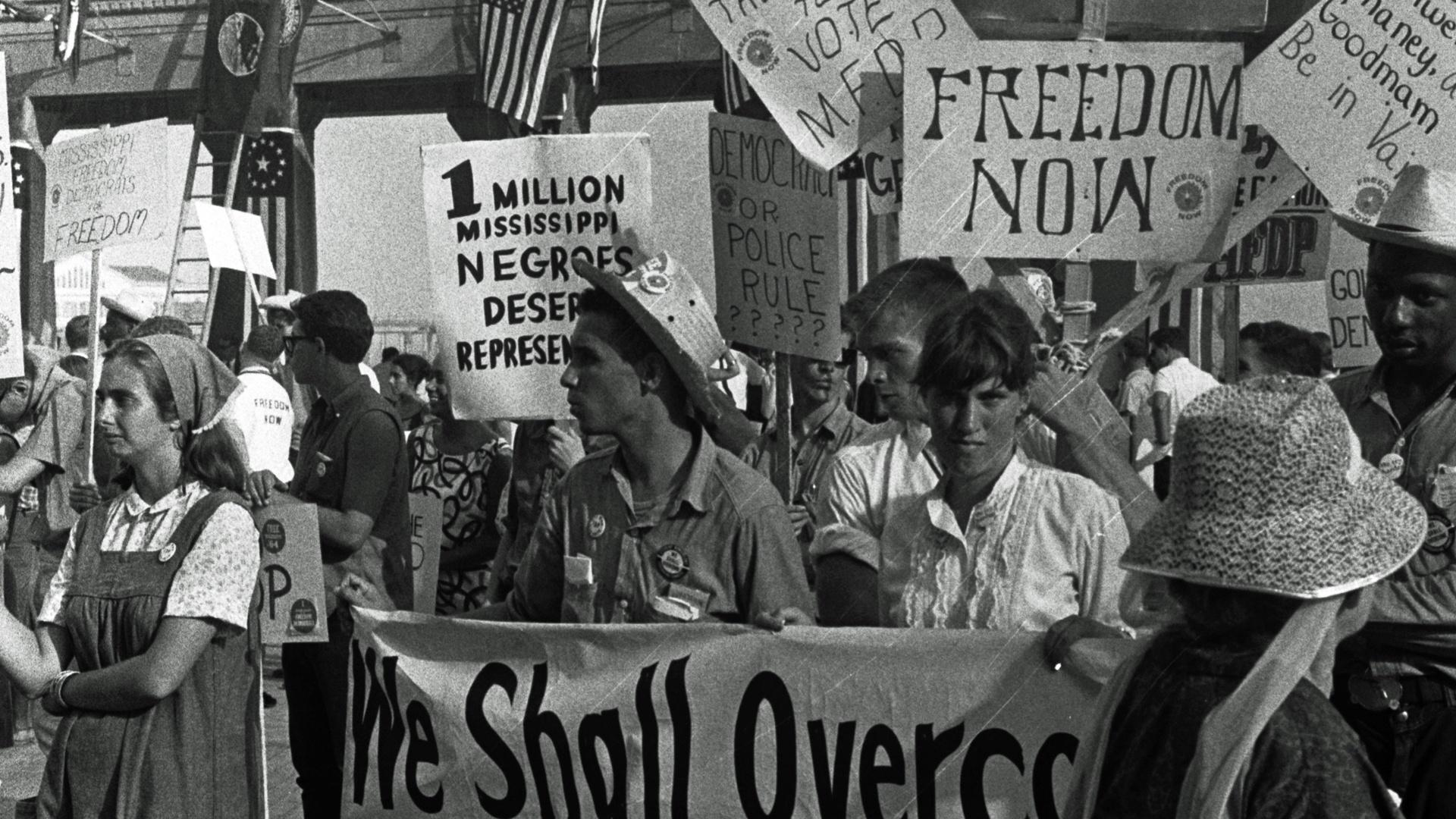African American and white supporters of the Mississippi Freedom Democratic Party holding signs in front of the convention hall at the 1964 Democratic National Convention, Atlantic City, New Jersey.