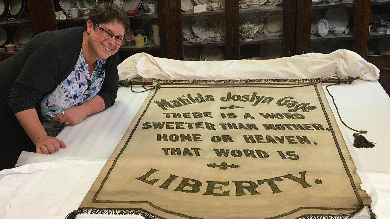 Lynne Bader poses in front of a Matilda Joslyn Gage banner