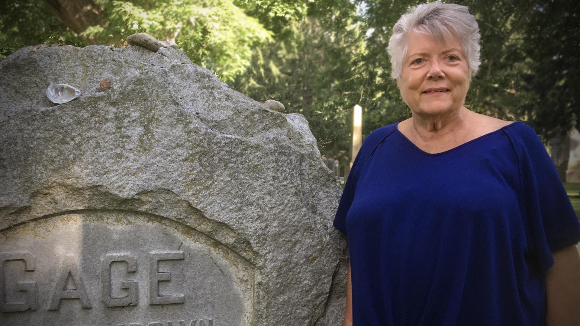 Sally Roesch Wagner stands in front of  Matilda Joslyn Gage's grave