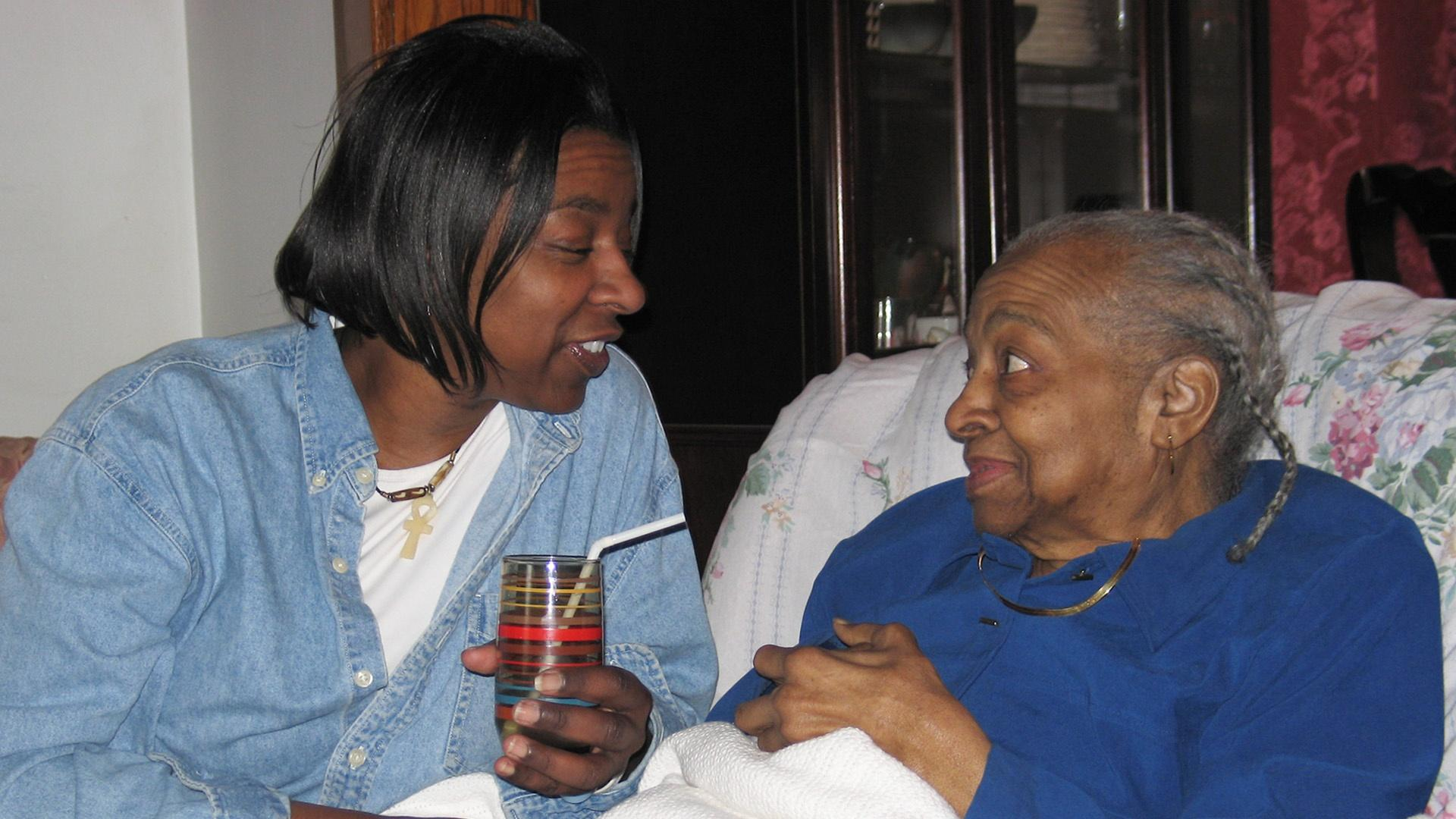 Caregiver checks in with her elderly loved one.