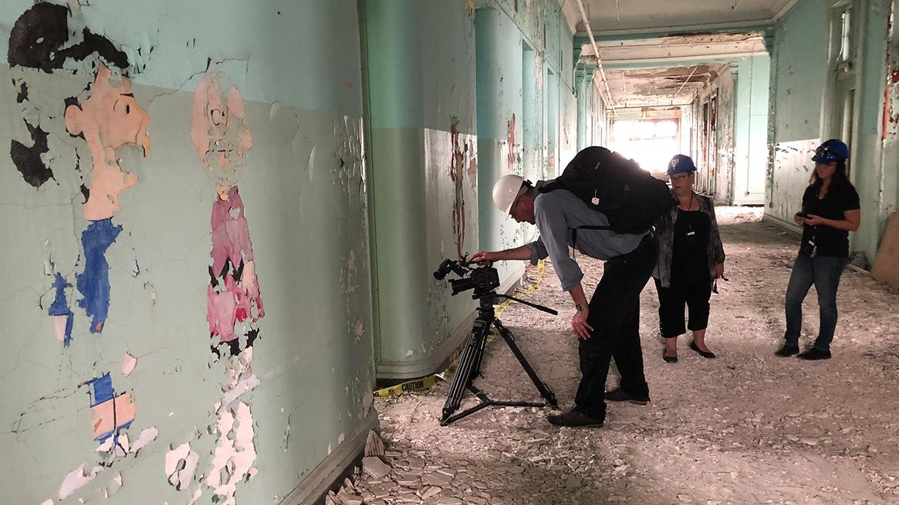 crew filming in one of the deteriorated sections of the campus
