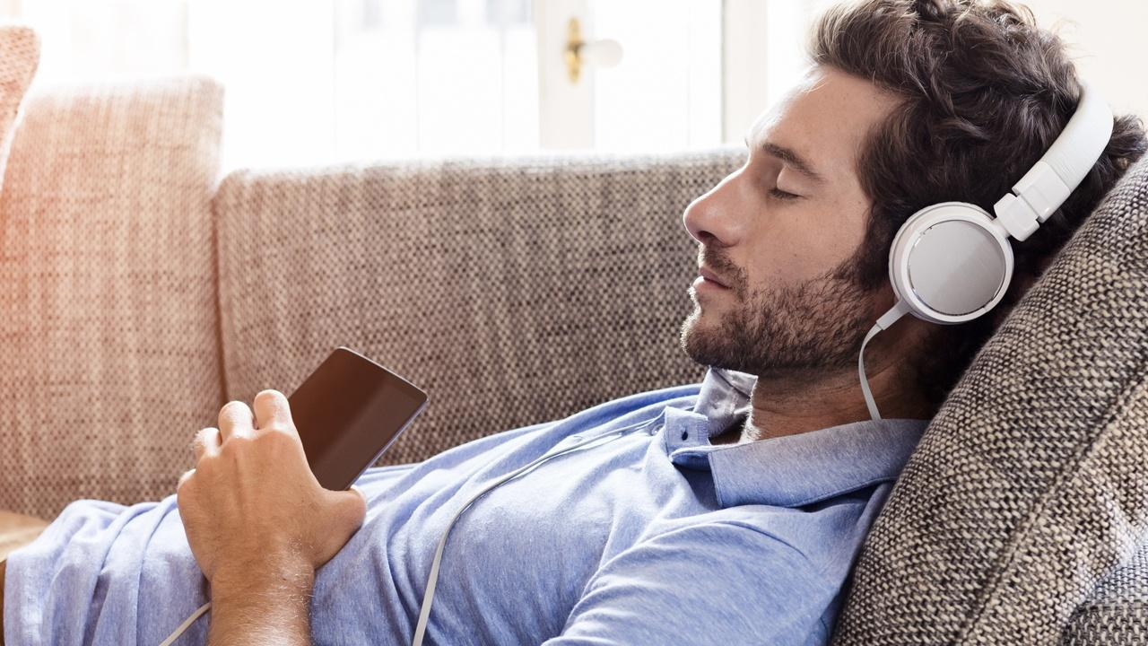 man listening to the radio with headset from his phone