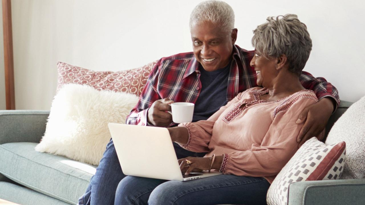 man and woman sitting on couch with laptop