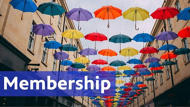 Membership text and colorful umbrella's floating between buildings.