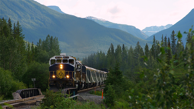 Train coming down the tracks surrounded by mountains and forests
