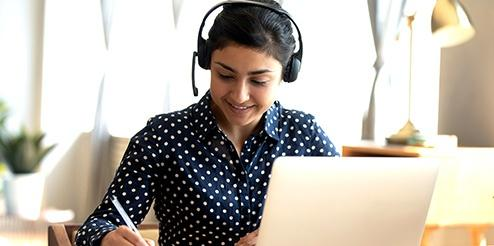 Woman on Laptop with Microphone headsets on
