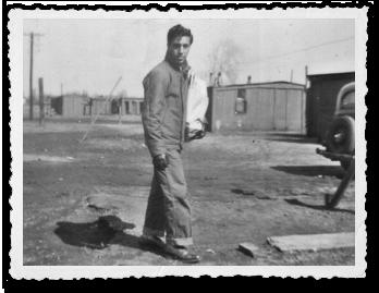 Man walking with a paper sack at Davis Camp
