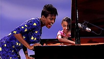 Pianist Jade Simmons explains how the piano works with a young girl