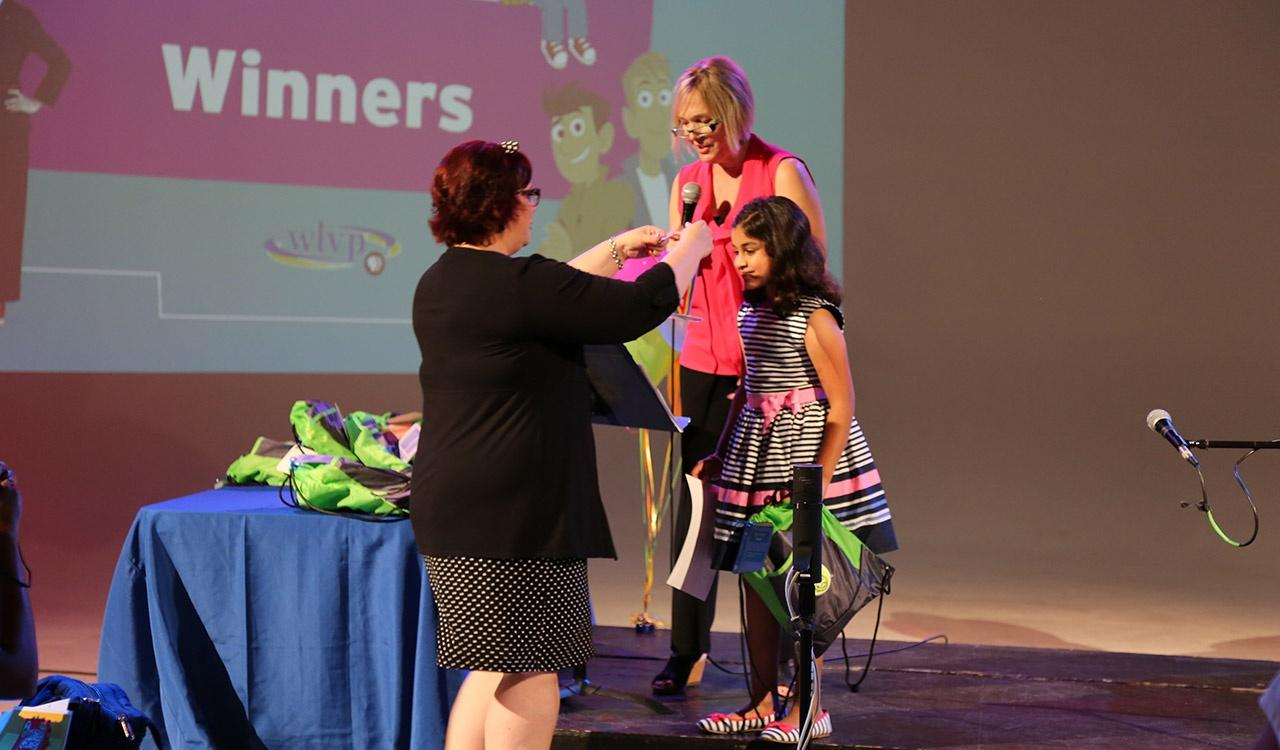 Julie giving a winner her medal at 2017 Writers contest
