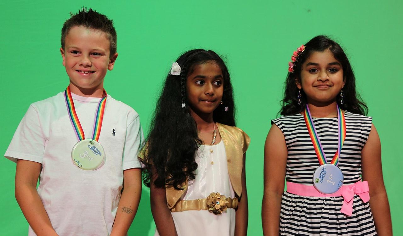 Three 2017 Writers Contest winners in front of green screen