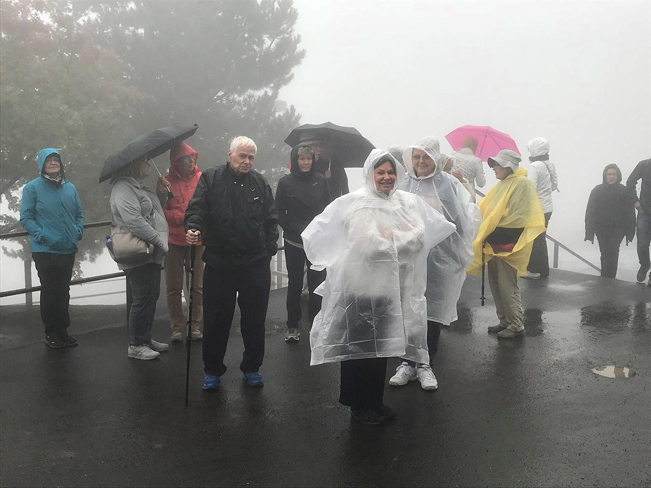 Group of travels in rain gear standing in the fog
