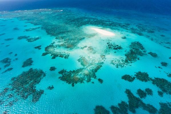 Aerial view of coral cay and Great Barrier Reef | Wonders of the World