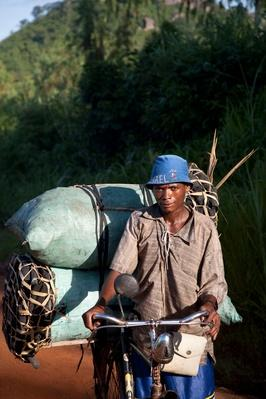 A Man Poses With His Heavy Cargo of Coal - Mozambique | Earth's Resources