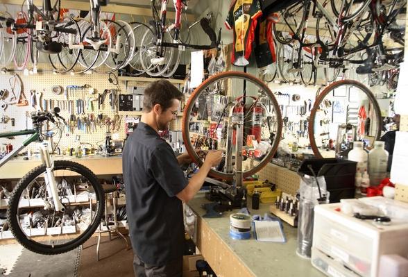 Bike shop owner fixes wheel | The Study of Economics
