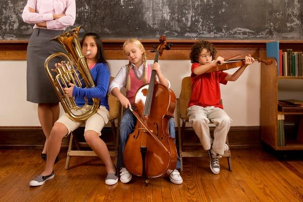 Three students playing musical instruments in a classroom | Musical Instruments