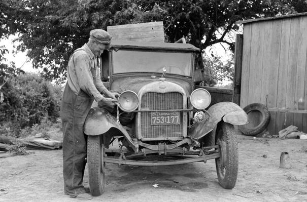 Migrant Man Working On Headlight Of An Auto | Ken Burns: The Dust Bowl