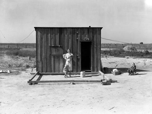 Woman Standing Outside Wooden Shack | Ken Burns: The Dust Bowl