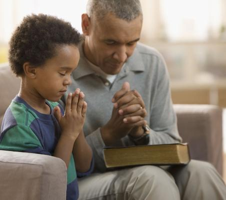 Grandfather and grandson praying together | World Religions: Christianity