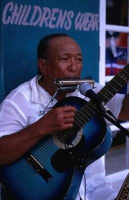 Local musician busking with harmonica and guitar in central Avarua | Musical Instruments