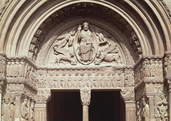 Detail of the church exterior showing the tympanum depicting Christ in Majesty with the four symbols of the evangelists and the lintel depicting seated figures of the twelve apostles