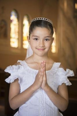 Hispanic girl with hands clasped in church | World Religions: Christianity