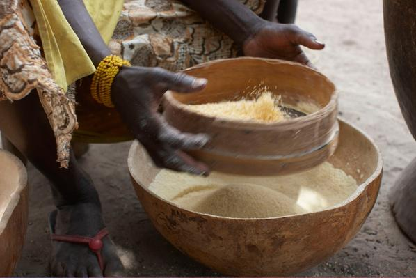 Woman Straining Corn Through a Sieve | Earth's Resources