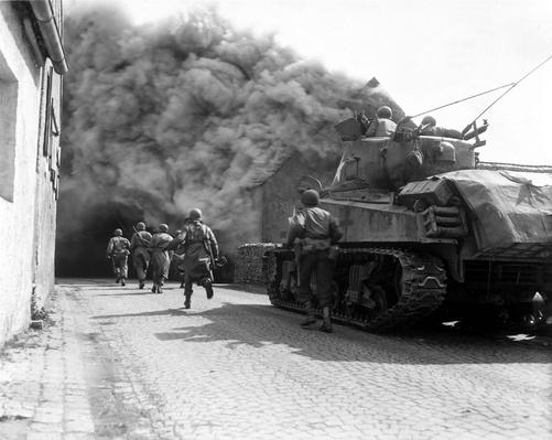 Soldiers move through a smoke filled street, Wernberg, Germany | World War II