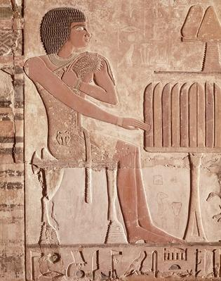 Relief depicting the deceased seated before an offering table with bread