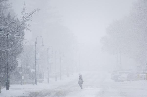 Person crossing a street during a snow storm in winter | Weather