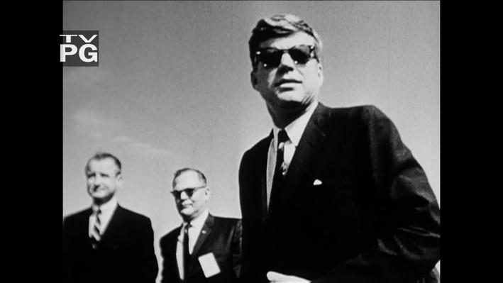 Black and white photo of JFK wearing sunglasses with two other men in the background.